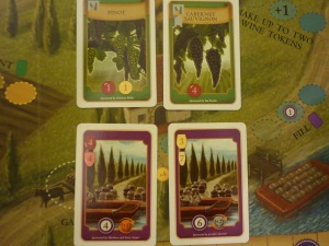 Green vine cards show what colour and value grapes are produced, and the symbols show what structures are required to plant them. The purple order cards show the wine types and value required and the victory points and residual order amount.